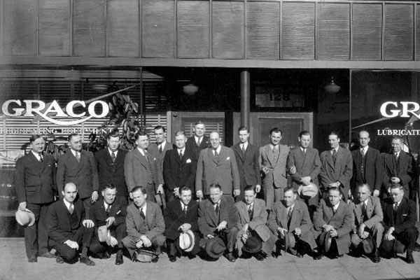 Men in front of Graco building