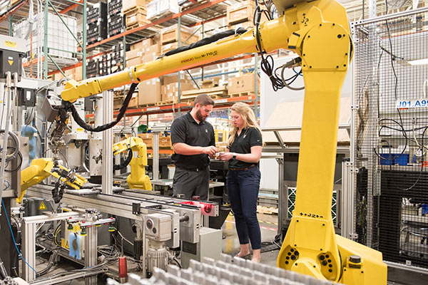 woman and man in factory with robot