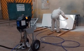 a man spraying a two-component amine cured, fast drying, high solid, high build epoxy coating.