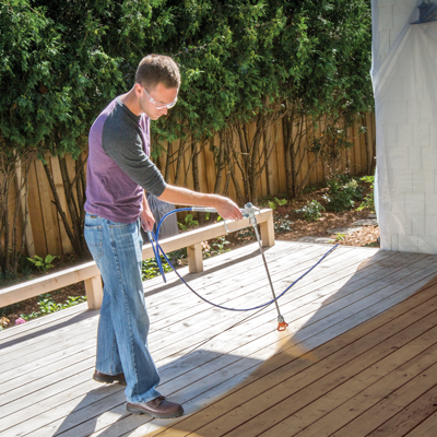 Man applying stain to decking using a sprayer with tip extension