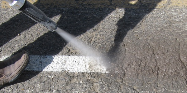 Removing parking lot lines with wet abrasive blasting
