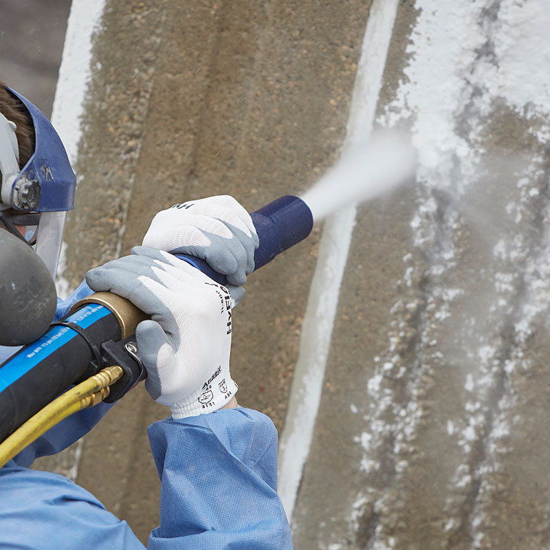 Man using blast nozzle on cement wall
