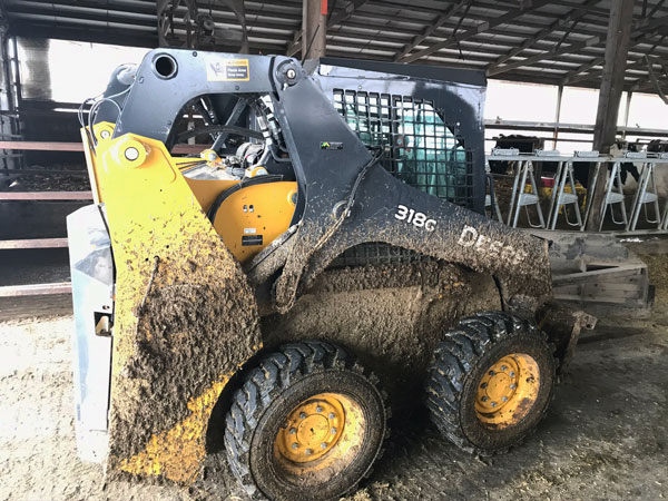 G-Mini auto lube pump on skid steer in cattle barn