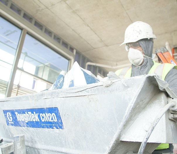 Contractor pouring bags into a plaster mixer