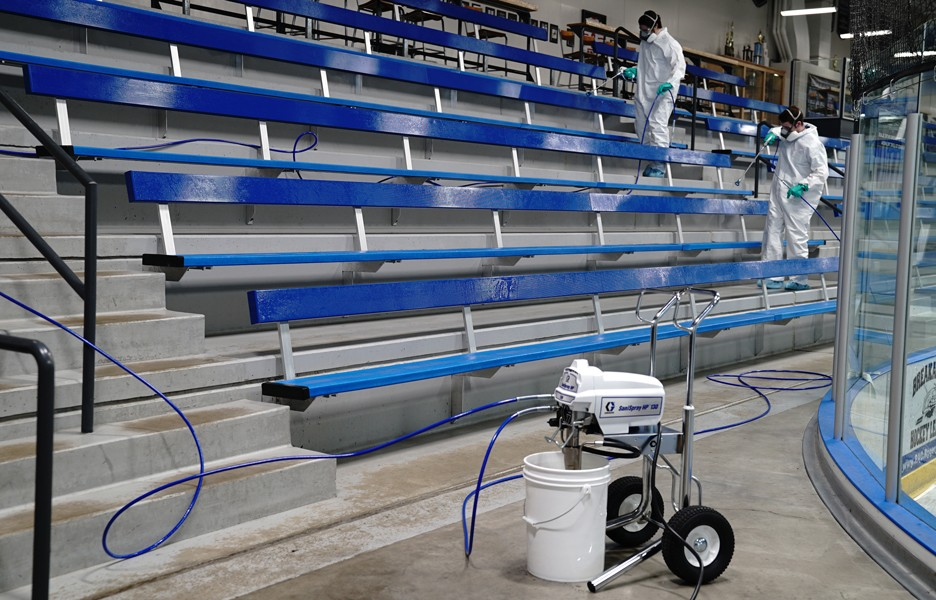 Graco SaniSpray HP 130 applying disinfectant to stands